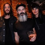 Ripley Johnson (center), guitarist and singer for Moon Duo, enjoyed a beer at his band's merch table after the their Oct. 11 show at Cafe Stritch. Johnson is flanked by keyboardist and vocalist Sanae Yamada (right) and Moon Duo's new drummer, John Jeffrey.
